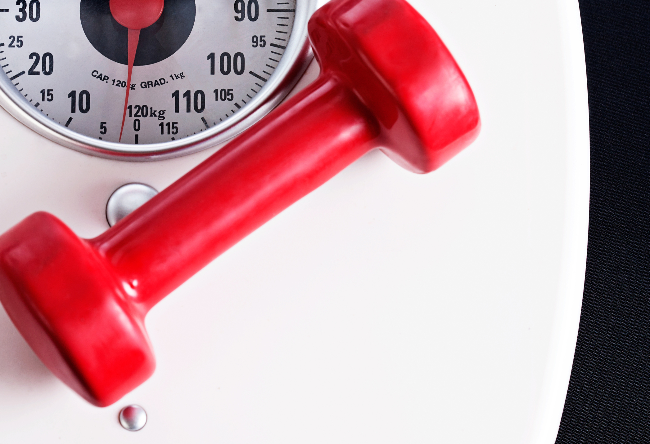 Single red barbell sits on domestic scale